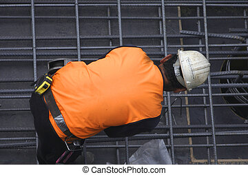 A tradesmen bends over to fasten steel mesh in place. A tedious job.