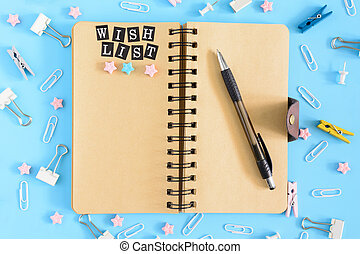 Wish list. Notepad with brown sheets and an inscription . Confusion of office supplies. Clips, clothespins and small sprockets scattered on a blue background.