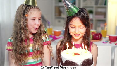 Little cutie making a wish and blowing out candles, her friend applauding