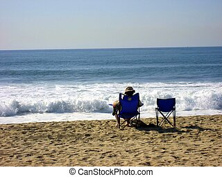 Wish You Were Here - Man relaxing in a chair at the beach...