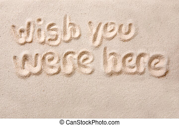 Wish you were here written in golden sand