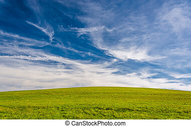 Wispy clouds over a grassy hill in York County, Pennsylvania.