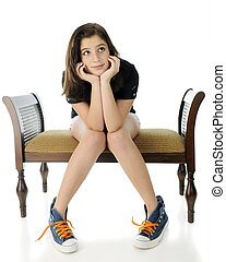 Wistful Tween - A pretty preteen girl wistfully sitting on a...