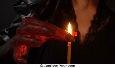 Witch extinguish the candle with hand - Footage of woman...