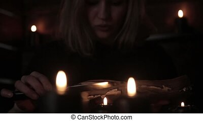 witch holds a knife and reading spell from old magic book lit by black candles.
