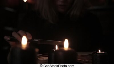 witch holds a knife and reading spell from old magic book lit by black candles