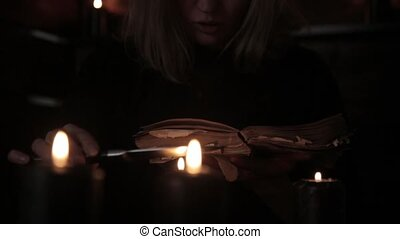 witch holds a knife and reading spell from old magic book...