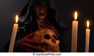 Witch looking at human skull - Footage of woman during...