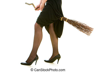 Image of female legs in black tights and black clothing riding on broom