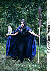 Witch with a bird in the forest