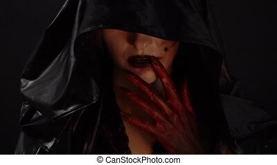 Witch with blood hands touching mouth - Footage of woman...