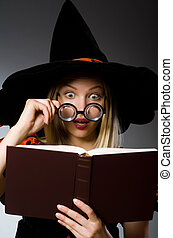Witch with book in dark studio