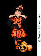 witch with jack o lanterns - child in halloween costume of...