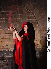 Gothic witch holding red smoke in a medieval castle