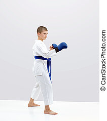 With a blue belt karateka boy is standing in the rack of karate