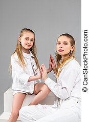 Pleasant young girl in white shorts and jacket attaching her...