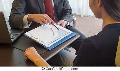Young dark-haired woman sitting back talking with her boss