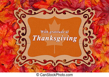 Thanksgiving greeting with red and orange fall leaves in a weathered wood frame