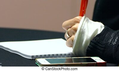 with his left hand to record information in a notebook - A...