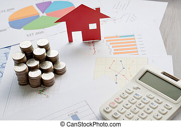 With House Model And Stack Of Coins On Desk
