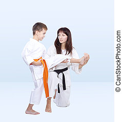 With orange belt athlete trainer teaches beat kick leg