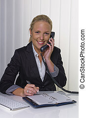 with phone in office - a friendly woman on the phone at her...