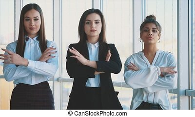With pleasure, three business women cross their arms, looking at the camera.
