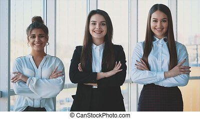 With pleasure, three business women with crossed hands