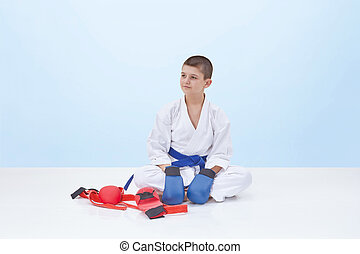 With the blue overlays on the hands of the athlete sits near a karate outfit
