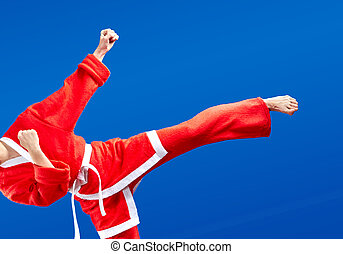 With white belt and in a suit of Santa Claus the sportswoman is beating kicking