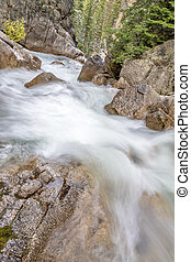 Wiver rapids curver over and around rocks in a river - Wild...