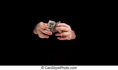 Wizard doing a trick with playing cards on black background, slow motion