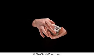 Wizard making his trick with cards on black background, slow motion