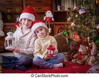 wo children with lanterns under Christmas tree