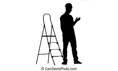Woker in a helmet stands near the stepladder. Silhouette. White background. Slow motion