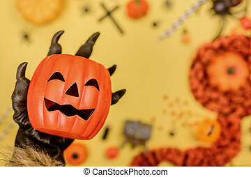 Wolf hand holding pumpkin face with Halloween background.Trick or treat in autumn and fall season.