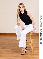 Beatiful blonde woman sitting on a barstool