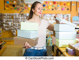 Woman 20-30 years old is choosing light boxes for gifts in store.