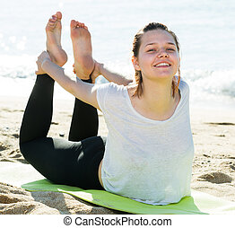 Woman 20-30 years old is practicing yoga in white T-shirt on the beach near sea.