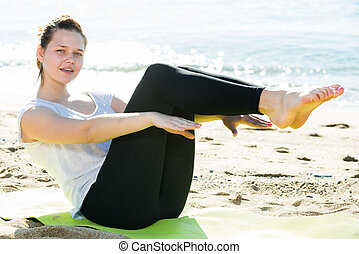 Woman 20-30 years old is stretching on in white T-shirt on the beach near sea.