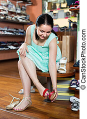 Woman 25-30 years old is trying on sandals for summer season in boutique.