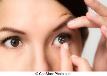 Woman about to place a contact lens in her eye - Woman about...