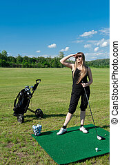 Woman about to strike golf ball