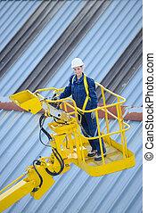 Woman above rooftops in cherry picker bucket