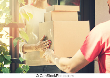 woman accepting a home delivery of boxes from delivery service courier