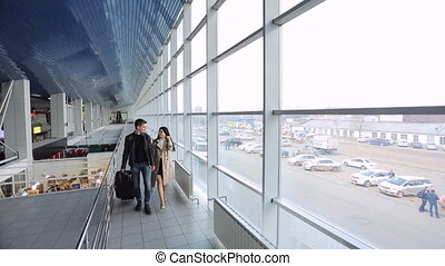 Woman accompanies a man on a trip, hold together for hands airport.