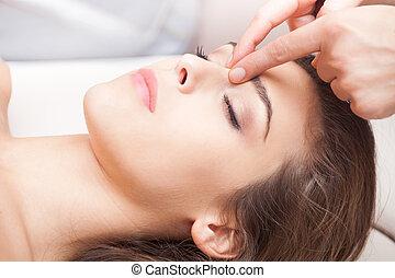acupressure - woman acupressure face massage closeup