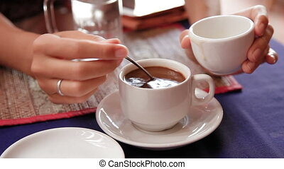 Woman adding coconut condensed milk in strong black coffee....
