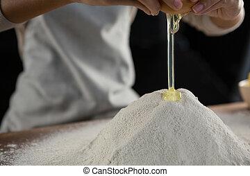 Woman adding egg white into flour