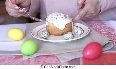 Woman adding sprinkles on the top of the Easter cake. Colored eggs on a table.